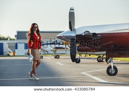 Beautiful girl in business style goes to the aircraft