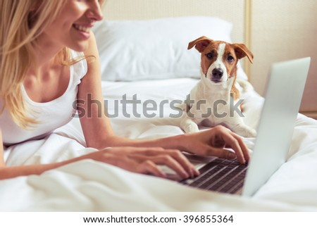 Beautiful girl in casual clothes is using a laptop and smiling while lying with her cute dog on bed, close up. Pet is looking at camera - stock photo