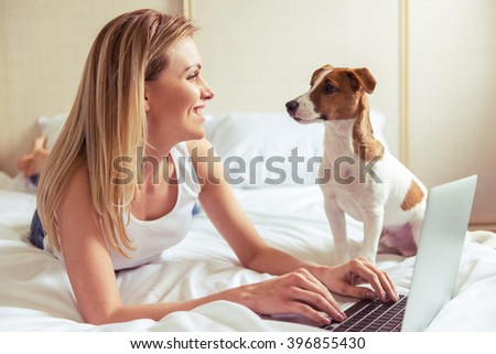Beautiful girl in casual clothes is using a laptop, smiling and looking at her cute dog while lying on bed - stock photo