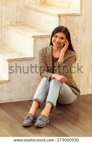 Beautiful girl in casual clothes talking on the phone and smiling while sitting near the wooden stairs