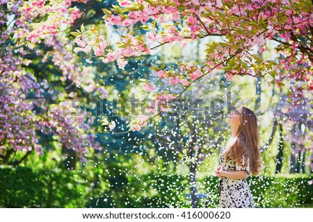 Beautiful girl in cherry blossom garden on a spring day, flower petals falling from the tree - stock photo