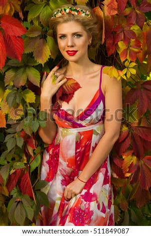 beautiful girl in color dress posing in autumn forest