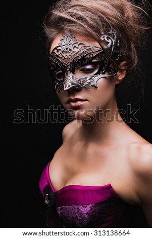 Beautiful girl in corset and mask with bright makeup . Beauty face.  Picture taken in the studio on a black background.