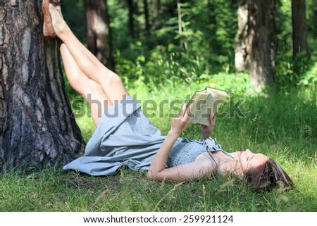 Beautiful girl in dress lying under tree on grass and reading book - stock photo