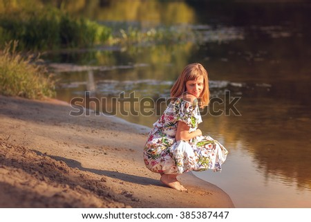 beautiful girl in dress on the river.