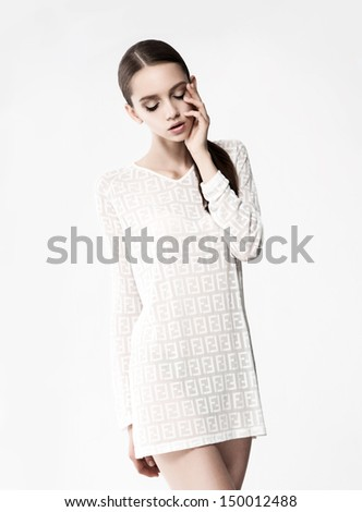 beautiful girl in  dress poses in front of  camera - stock photo