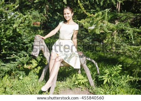 beautiful girl in dress sitting on a funny little wooden horse in the park