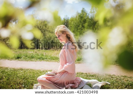 beautiful girl in dress sitting under the apple blossom