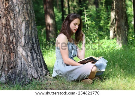 Beautiful girl in dress sitting under tree on grass and reading book - stock photo