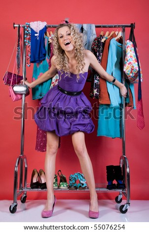 beautiful girl in fashion clothes in the dressing room on a red background - stock photo