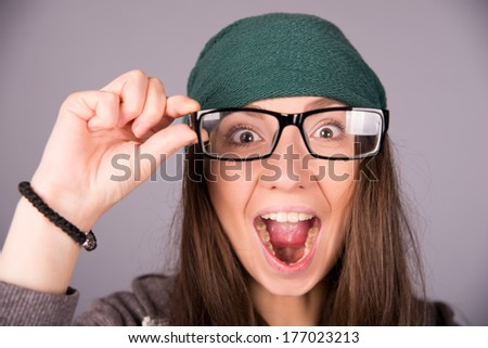 beautiful girl in glasses on gray background