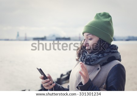 Beautiful girl in green hat and coat reads the message, she is disappointed or surprised news. - stock photo
