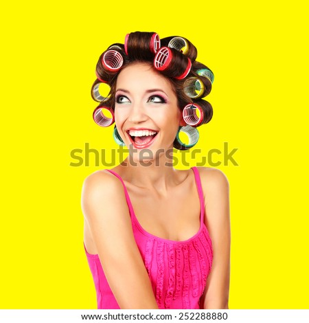Beautiful girl in hair curlers on yellow background - stock photo