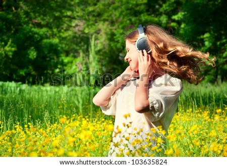 beautiful girl in headphones enjoying the music with flowing hair in a field of flowers in nature - stock photo