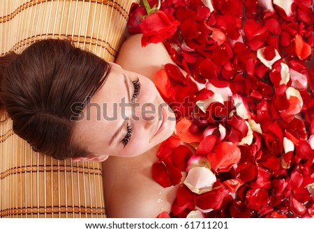 Beautiful girl in jacuzzi with rose petal. - stock photo