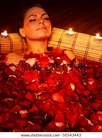Beautiful girl in jacuzzi with rose petal and candle. Body care. - stock photo