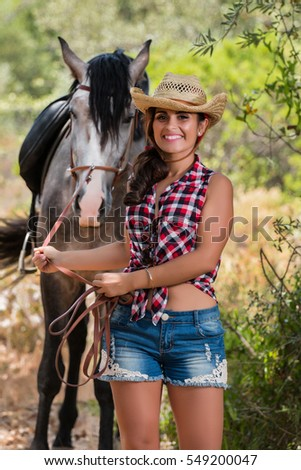 Beautiful girl in jeans and straw hat with an horse in nature.