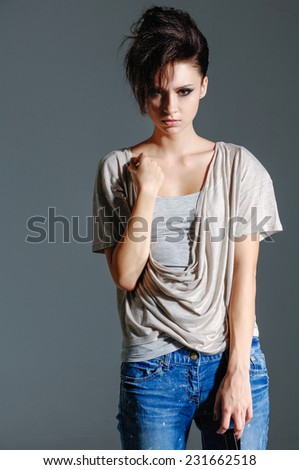 beautiful girl in jeans posing-gray background   - stock photo