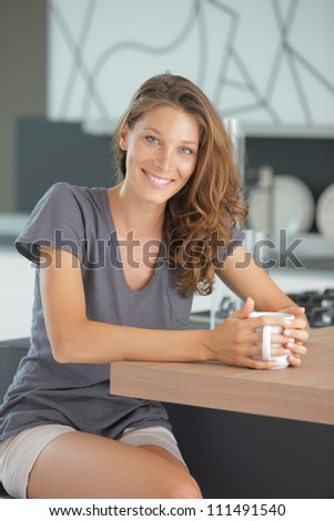 Beautiful girl in kitchen with a cup of cofee or tea - stock photo