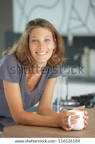 Beautiful girl in kitchen with a cup of coffee or tea - stock photo