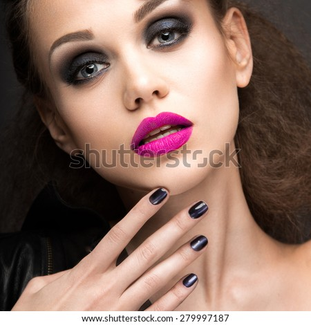 "Beautiful girl in leather jacket with bright makeup and manicure ""Cat's Eye"". Beauty face. Nail Design. Picture taken in the studio on a black background."