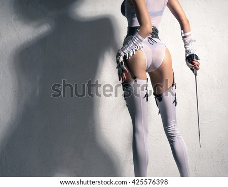 beautiful girl in lingerie stands with a whip against the wall - stock photo