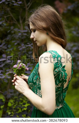 beautiful girl in long green dress on a background of spring foliage with a bouquet of lilac flowers