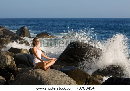 Beautiful girl in lotus position on the stone. Splashes of sea waves. Evening light. - stock photo