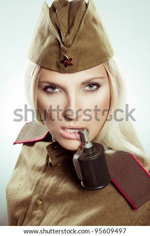 Beautiful girl in military clothes with grenade.