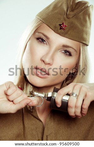 Beautiful girl in military clothes with grenade. - stock photo