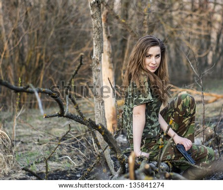 Beautiful girl in military uniform in the woods