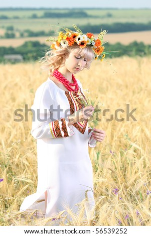 beautiful girl in national dress and a wreath in the field of wheat - stock photo