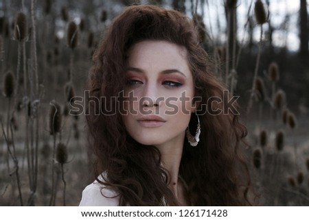 Beautiful girl in nature with long curly red hair - stock photo