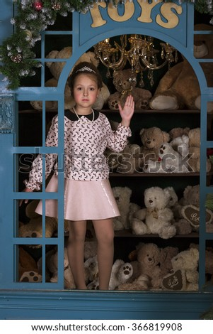 Beautiful girl in pink dress portrays a porcelain doll in the window with plush bears, background for Valentine's day celebration