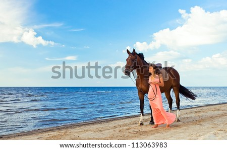 beautiful girl in pink dress with horse on seacoast