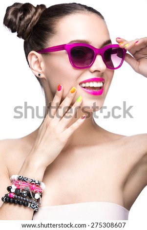 Beautiful girl in pink sunglasses with bright makeup and colorful nails. Beauty face. Picture taken in the studio on a white background.