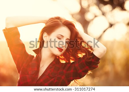 Beautiful girl in plaid dress on sunset at countryside  - stock photo