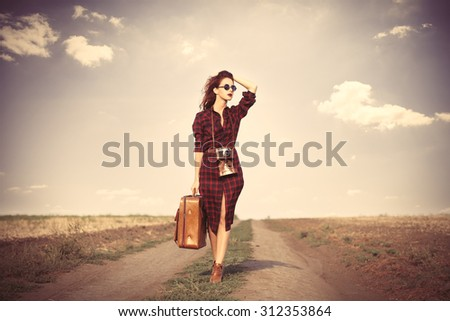 Beautiful girl in plaid dress with bag and retro camera on countryside - stock photo