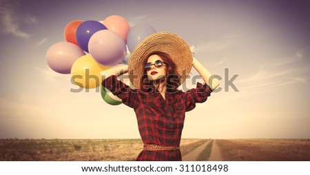 Beautiful girl in plaid dress with multicolored balloons on countryside