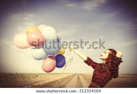 Beautiful girl in plaid dress with multicolored balloons on countryside - stock photo
