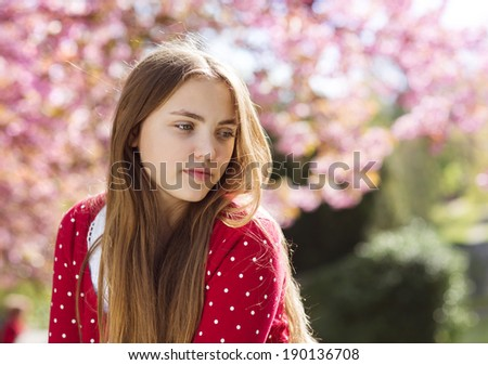 Beautiful girl in red cardigan lying relaxing in spring garden with blooming trees - stock photo