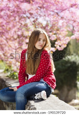 Beautiful girl in red cardigan sitting on a wall in spring garden with blooming trees - stock photo