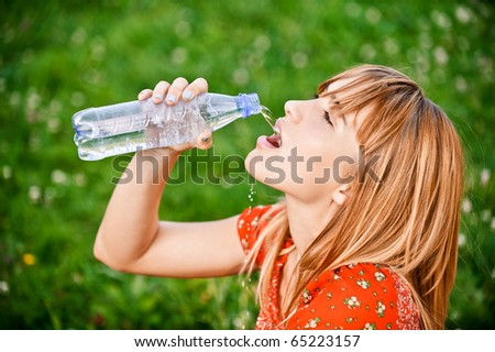 Beautiful girl in red dress drinks water from bottle, against green grass. - stock photo