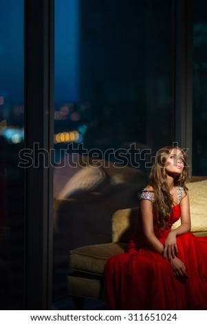 Beautiful girl in red dress indoors - stock photo