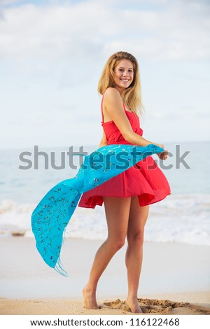 Beautiful Girl in Red Dress on The Beach. Travel and Vacation. - stock photo