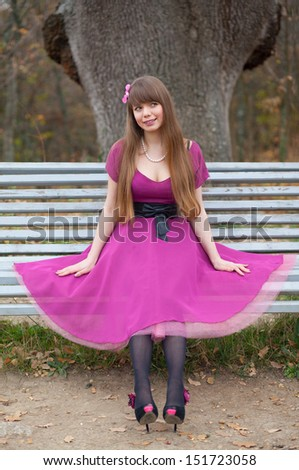Beautiful girl in red gown sits on bench