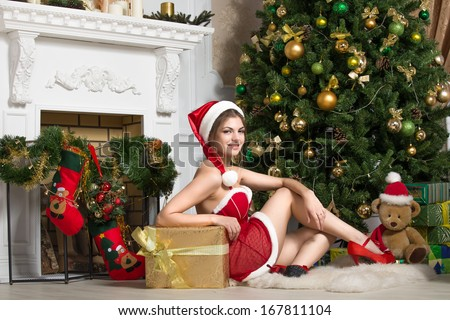 Beautiful girl in red party clothes sitting near the Christmas tree - stock photo