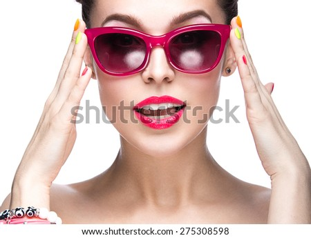 Beautiful girl in red sunglasses with bright makeup and colorful nails. Beauty face. Picture taken in the studio on a white background.