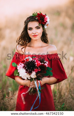 beautiful girl in red with a bouquet of flowers