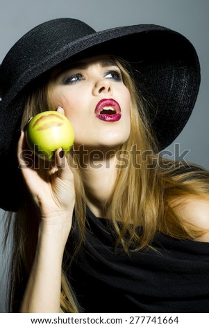 Beautiful girl in retro black hat with bright make up looking away holding fresh green apple standing on gray background copyspace, vertical picture - stock photo